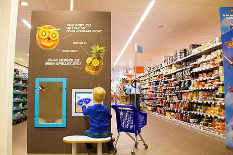This picture shows a boy playing at the Albert Heijn kids corner supermarket
